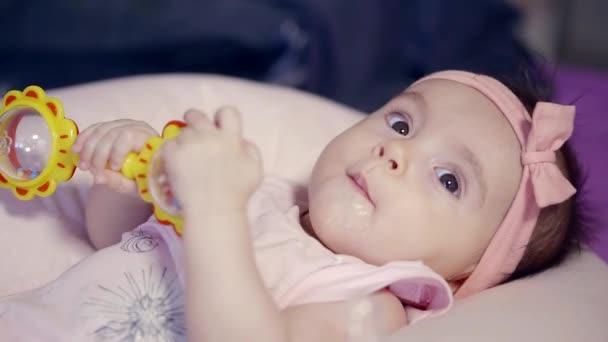 Roztomilé kojenecké dívka leží v posteli s její hračka samotná