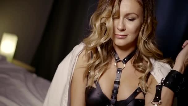 attraktive, fröhliche Frau sitzt in einem Schlafzimmer abends allein, trägt schwarze erotische Dessous
