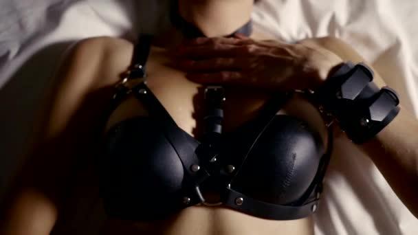Domina Frau liegt auf einem Bett, sie trägt erotische Leder Dessous und schwarze Maske für Petplay