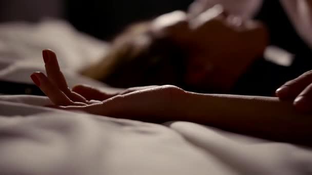 Hände eines Liebespaares während Sex im Schlafzimmer in der Nacht, Mann ist Womans Hand streicheln.