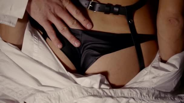 Mann ist einen Womans Arsch unter schwarzen Höschen und sie zurück in Lederriemen gekleidet streicheln.