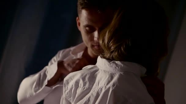 Mann zieht ein weißes Hemd von blonden Frau trägt Lederunterwäsche in dunklen Raum