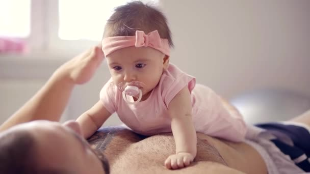 cute baby girl with baby pacifier is lying on belly and chest of her