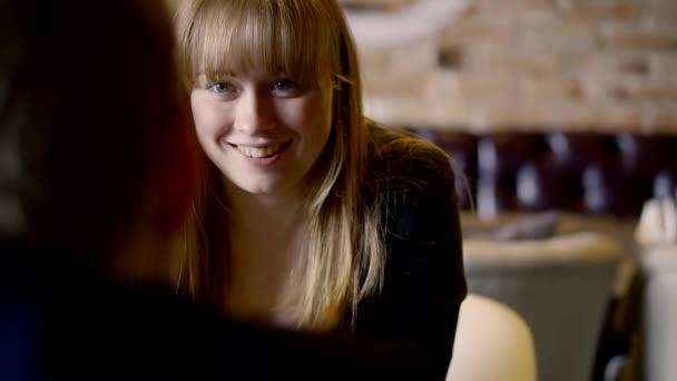 niedliche Frau ist im Café bei einem Date, die Dame flirtet lächelnd, während sie auf ihre Bestellung wartet