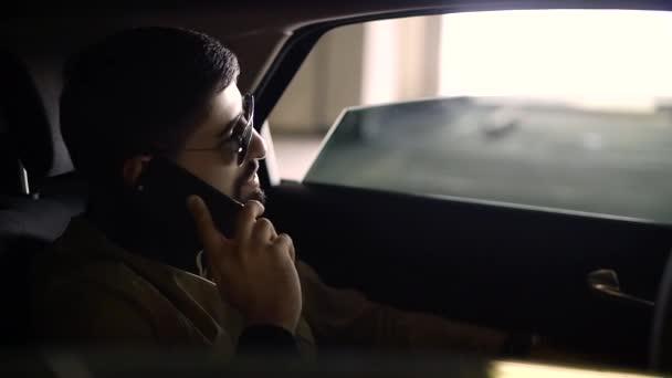 5191ff4796 Un hombre joven en gafas de sol con un smartphone caro en su mano y hablar  por teléfono en el coche– metraje de stock
