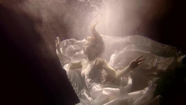 podvodní Kouzelná víla se topí v temnotě, velkých bílých šatech je plovoucí kolem, je v cloudu