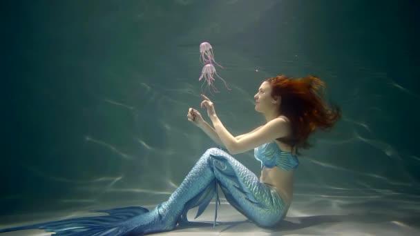 žena s ocáskem mořské panny je sedí dně oceánu a hrát si s dvěma růžové jellyfishes, doteku