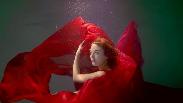 hezká mladá žena s dlouho jasně červené látky plovoucí kolem ní je pod vodou, Detail obličeje