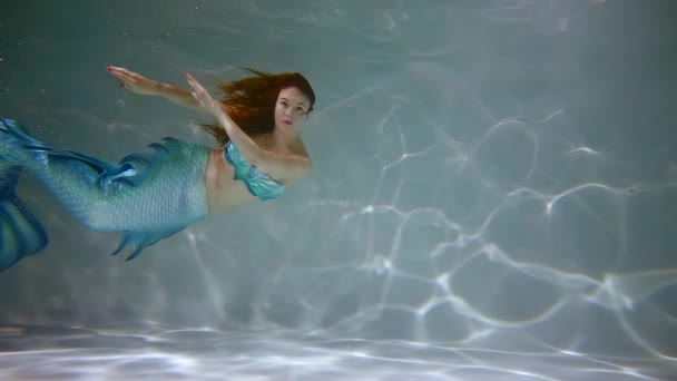 young woman is wearing mermaid costume floating in a pool under water, famous fairy character