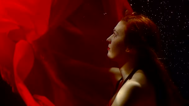 underwater nymph with long red hair and red dress is floating in a natural reservoir in darkness