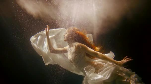graceful fashion girl is wearing long dress and swimming underwater in a supernatural light and air bubbles