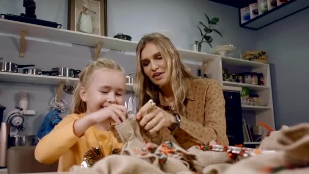 Charming young mother and her sweet daughter playing with Christmas ...