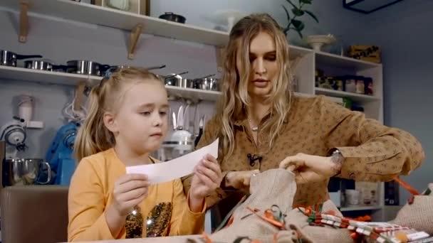 dívka dítě žádá její matka číst poznámky z taštička od Santa. Ráno po Silvestr v kuchyni