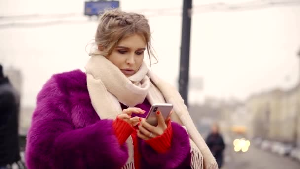a young woman in a winter and a warm coat holds a smartphone and prints a message for her friends
