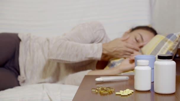 eine junge Frau misst die Temperatur mit einem Thermometer, sie liegt auf dem Bett und ist krank