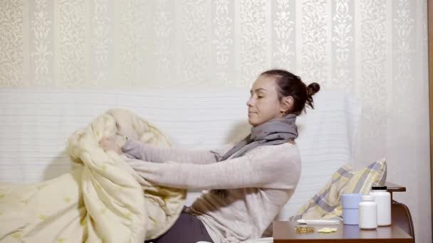 eine junge Frau, die krank wird, aus dem Bett steigt, um die Temperatur zu überprüfen und Medizin zu trinken