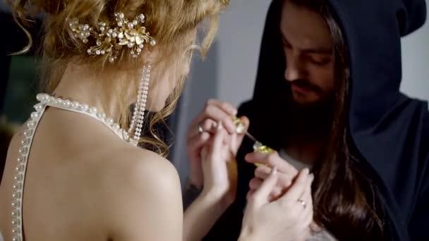 ein erwachsener Mann mit langen Haaren und eine Kapuze auf seinen Kopf arbeiten wie ein Parfümeur, gibt er einen Versuch zu riechen Duft einer Frau