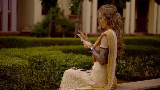 mladá Evropská žena používá telefon pro komunikaci na internetu, cestuje v letním období do Asie