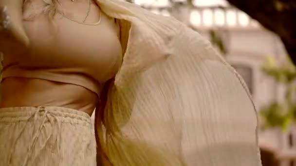 Nahaufnahme des Körpers einer Frau, die während eines alten und traditionellen Tanzes Kleidungsstoffe entwickelt