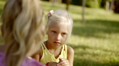 The older sister tells the younger terrible story in the park in the summer, the girl reacts to it very emotionally