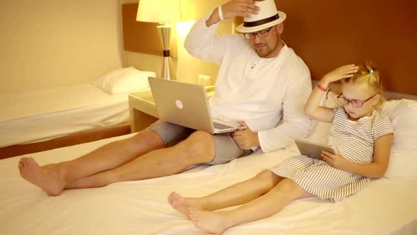 ein erwachsener Mann und ein Kind verbringen Zeit miteinander, ein Mann hält einen Laptop und eine Tochter ein Tablet, ein Vater liebt ein Kind
