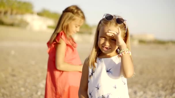 Zwei kleine Mädchen stehen am Strand in der Nähe des Meeres, ein Kind mit Sonnenbrille blickt geradeaus und verdeckt sein Gesicht vor der Sonne