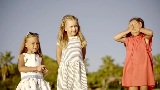 Little girls are standing in nature, a child is picking up a pebble from the ground, cute and funny children