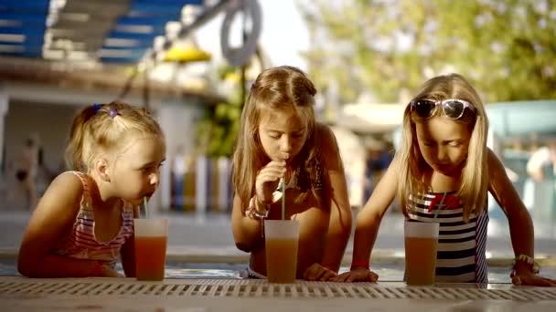 Drei Mädchen mit Begeisterung trinken Orangensaft im Pool, Kinder genießen Sie eine leckere und erfrischende Getränk