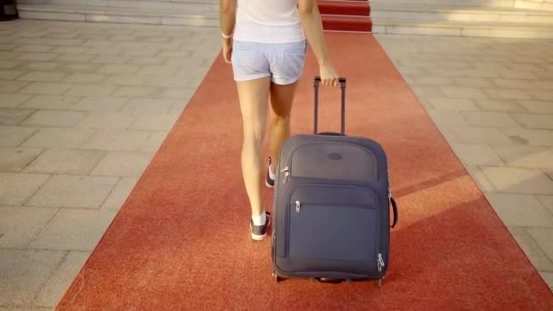 A woman or a girl carries a suitcase by the handle, the lady steps along the road, which is covered with a red carpet