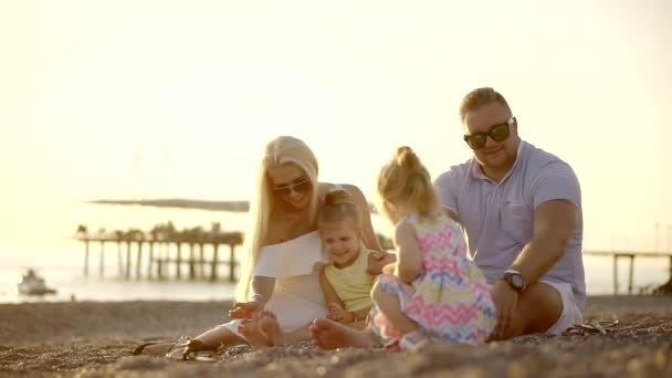 Parents and their children spend time on the beach on a summer day, the family sits near the sea on a stone beach