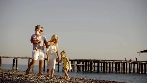 Parents and their children spend time on the beach, the family walks along the stone beach, the husband carries a daughter in her arms