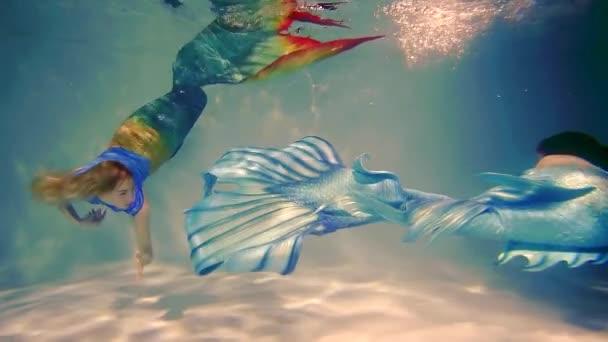 roztomilý štíhlé dívky s ocásky ryby plavat ve vodním sloupci. Fantastické bytosti mořské panny
