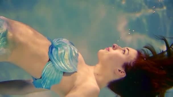 detail. mořská panna dívka je ve stavu beztíže ve vodě. Dlouhé zrzavé vlasy