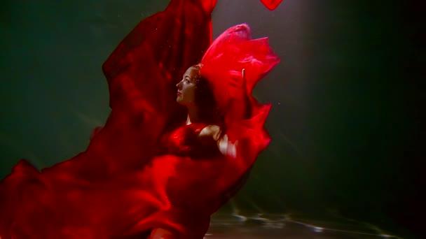 mladá žena s dlouhými tmavými vlasy v červených šatech, plavání pod vodou jako v pohádce