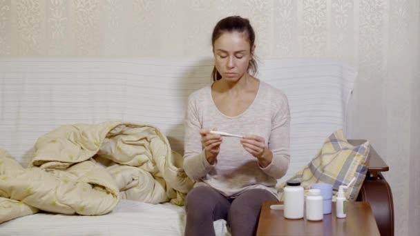 Frau nimmt Temperatur sitzend auf der Couch