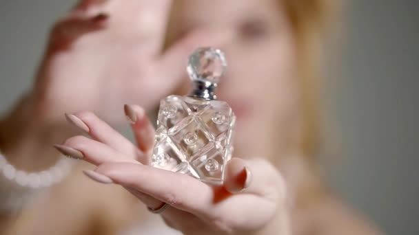 Close up shot of expansive perfume bottle in the hand of beautiful woman.