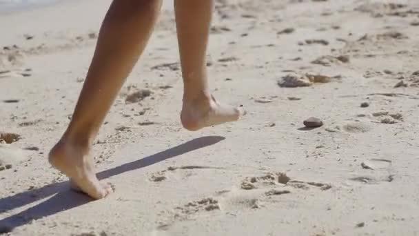 Detailní záběr záběr Zenske nohy běží na písečné pláži