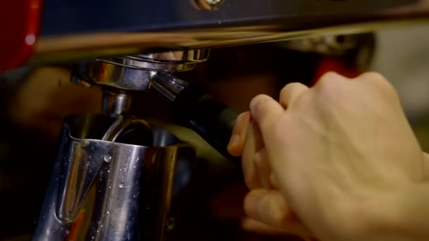 Close up shot of a barista making coffee in coffeemaker indoor.