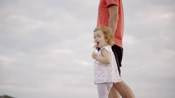 Father and daughter are walking on the beach