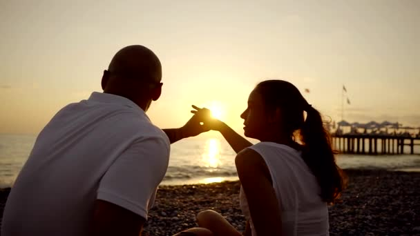 Beautiful couple is sitting on the beach during sunset