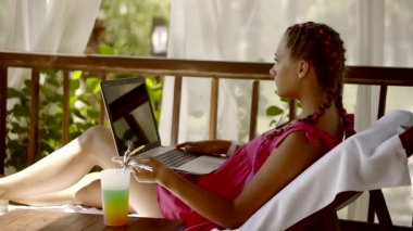 Attractive woman lies in launger with a laptop