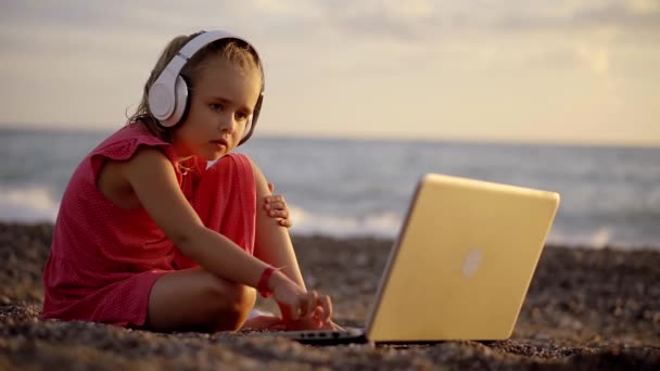 Little girl is watching cartoons on the beach