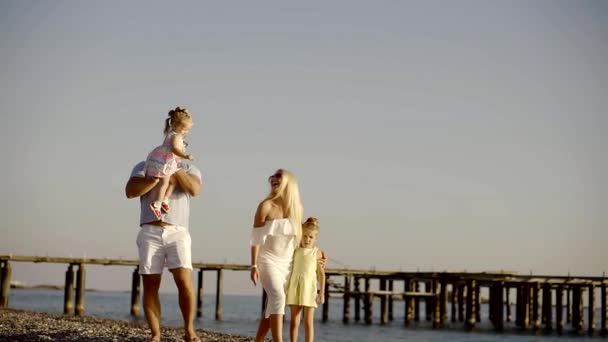 Happy family is walking on the beach together.