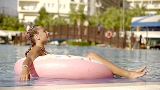 Donna felice in piscina sotto il sole