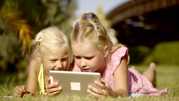 Fiatal lányok hanyatt fekszik a pázsiton, és játék játékok-ra tabletta.