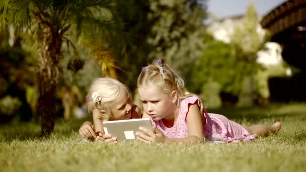 Little sisters néz rajzfilmeket hanyatt fekszik a pázsiton.