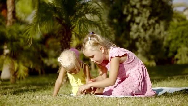 Imádnivaló kis lányok játszanak a gyepen.
