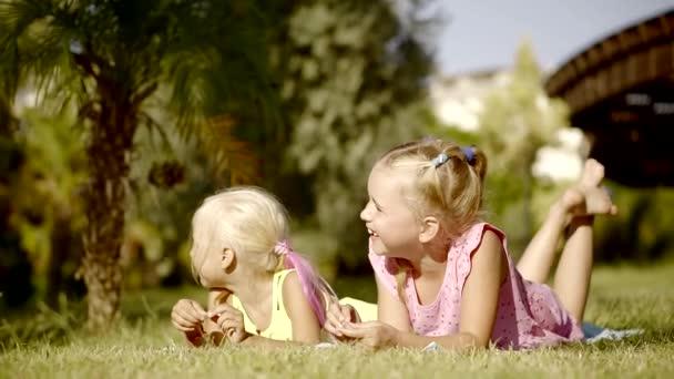 Csinos lányok hazudik a gyepen a takarót