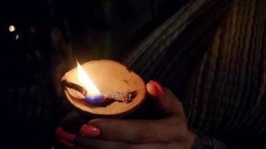 womans hands are holding lighted ancient clay oil lamp in dark church
