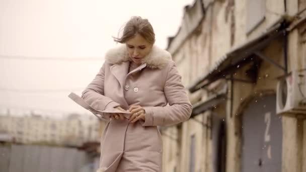 einsame junge Frau steht auf einer Straße mit alten Häusern, im Slum, an einem kalten, windigen Wintertag, es schneit